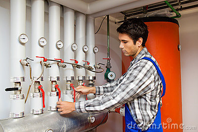 Heating engineer in a boiler room for heating