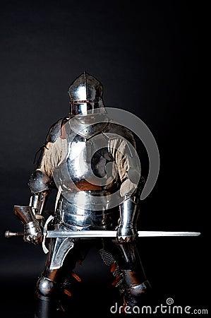 Heavy armoured man holding his sword
