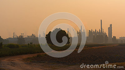 Heavy industrial plant against agriculture field. Stock Photo