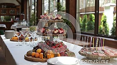 Heerlijke verfraaide snoepjes en vruchten op lijsten, de catering van de cocktailspartij stock video