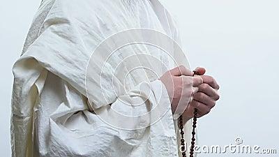 Helderziende die aan God bidt die gebedparels aan tekenherhalingen van gebeden, rozentuin gebruikt stock videobeelden