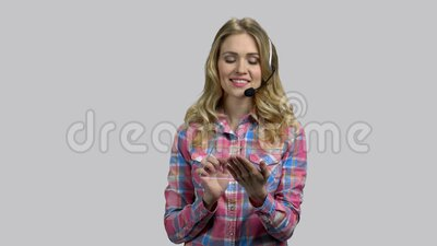 Helpdesk worker, young girl with headset and blank glass tablet. Grey isolated background stock footage