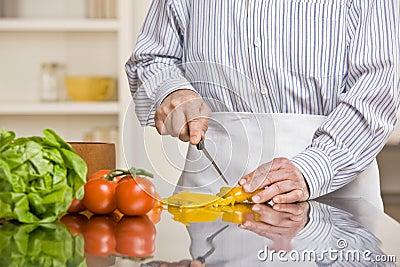 Helpful man preparing salad in kitchen