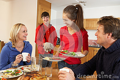 Helpful Teenage Children Serving Food To Parents