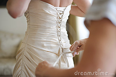 Helping a bride to put her wedding dress on