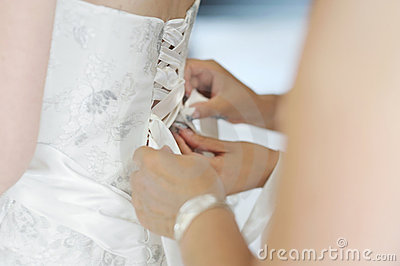 Helping the bride to put a wedding dress on