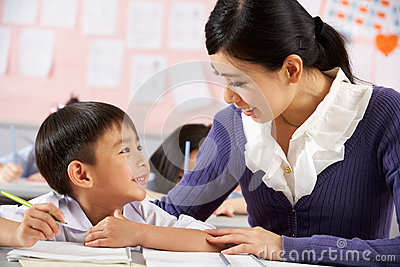 Helping Student Working At Desk In Chinese School