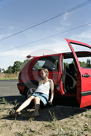 Helpless pregnant woman sitting near red car