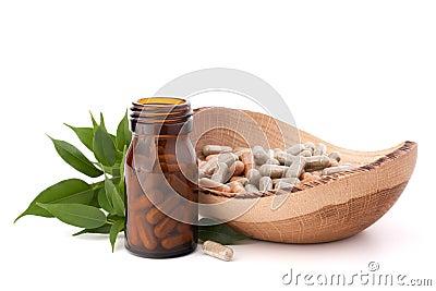 Herbal drug capsules in brown glass bottle. Alternative medicine