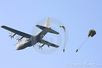 Hercules plane drops parachute troopers Editorial Stock Image