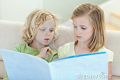 Hermanos que leen el compartimiento en el sofá