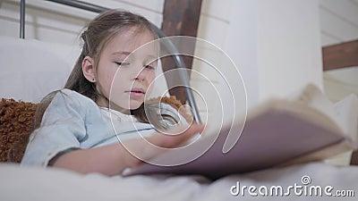 Hermosa chica caucásica con ojos grises sosteniendo el libro y leyendo Retrato de la pequeña dama en la cama hobby, felicidad almacen de video