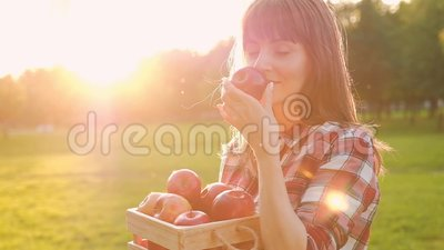 Hermosa joven vestida de forma casual inhala el aroma de una manzana fresca madura almacen de metraje de vídeo