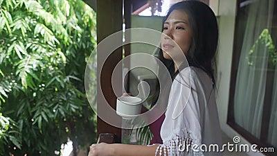 hermosa mujer asiática coreana tomando café o té por la mañana en la terraza del hotel cortinas puerta o balcón de la casa sonrie almacen de video