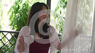 Hermosa mujer asiática coreana tomando café o té por la mañana en la terraza del hotel cortinas puerta o balcón de casa sonriente metrajes