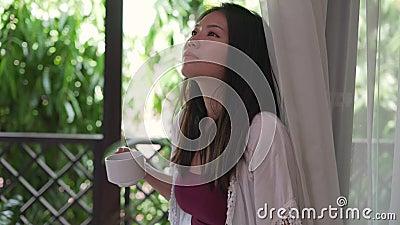 Hermosa mujer asiática coreana tomando café o té por la mañana en la terraza del hotel cortinas puerta o balcón de casa sonriente almacen de video