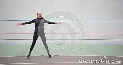 Hermosa mujer delgada hace ejercicios cardiovasculares matutinos saltando botes en el fondo blanco afuera metrajes