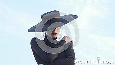 Hermosa mujer misteriosa en negro abrazándose sensualmente almacen de video