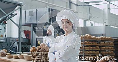 Hermosa mujer panadera sonriendo bastante delante de la cámara de fondo gran industria de panadería y hombre panadero moviéndose  almacen de metraje de vídeo