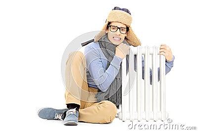 Het bevriezen van jonge kerel in van de de winterhoed en sjaal zitting naast radia