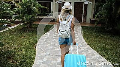 Het blonde meisje in een hoed en overall regelt in een tropisch hotel met een blauwe zak stock footage