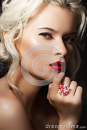 Het blonde model van de luxe met rode lippen & heldere juwelen