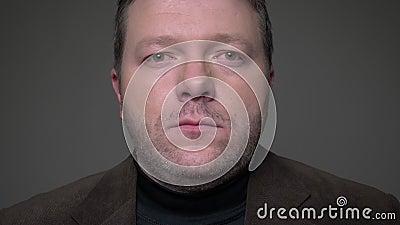 Het close-upportret van donkerbruine zakenman op middelbare leeftijd in kostuum heft blik het letten vreedzaam op in camera op gr stock video