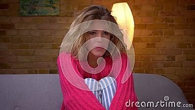 Het close-upschot van ontspannen huisvrouw in roze sweaterhorloges filmt aandachtig bij comfortabel huis stock footage