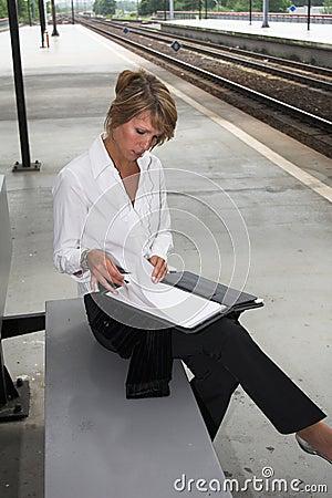 Het controleren van haar nota s bij trainstation