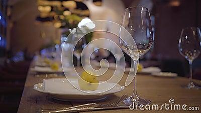 Het dienen van een lijst in een duur restaurant Lege wijnglazen, witte platen, bestek op een houten lijst Sappige citroenen stock footage