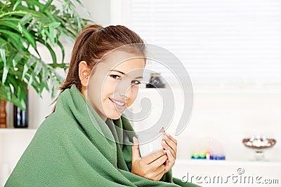 Het drinken van de vrouw thee die thuis met deken wordt behandeld