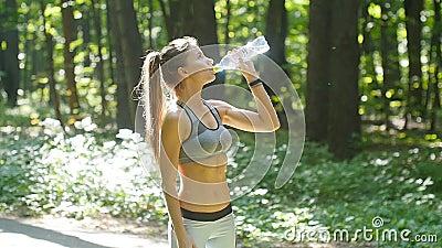 Het drinkwater van de geschiktheidsvrouw van fles in zonnig bos stock footage