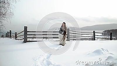Het etnische meisje met lang haar neemt door de afwijkingen heimelijk Op de achtergrond is een houten omheining en bergen snowing stock videobeelden