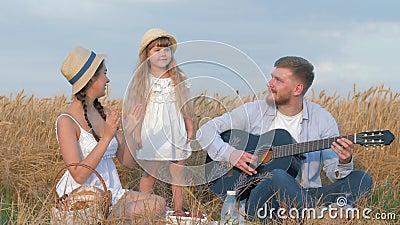 Het familie in openlucht vermaak, jonge man speelt gitaar terwijl zijn vrouw en weinig leuke dochter in strohoeden en wit stock video
