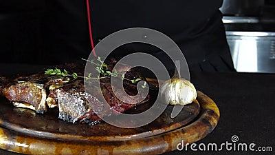 Het gebraden lapje vlees op de grill ligt op een houten raad met groenten stock footage