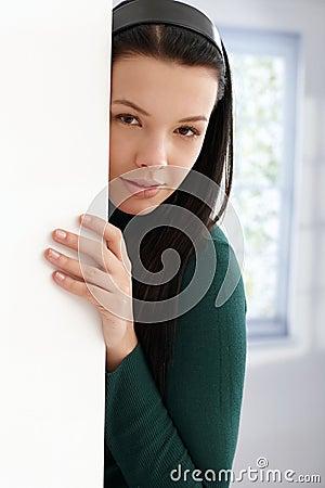 Het geheimzinnige jonge vrouwelijke verbergen achter muur