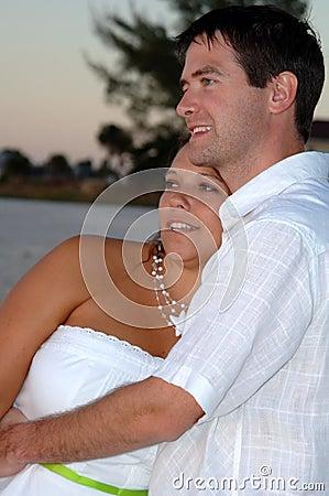 Het gelukkige Paar omhelst op strand