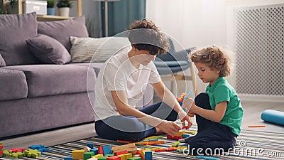 Het gelukkige van het familiemamma en kind spelen met speelgoed die thuis op vloer samen zitten stock footage