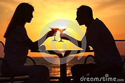 Het gerinkelglazen van het paar op zonsondergang buiten