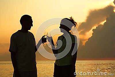 Het gerinkelglazen van het paar. Silhouetten tegen overzees.