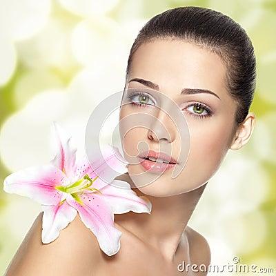 Het gezicht van de schoonheid van jonge vrouw met bloem. De behandelingsconcept van de schoonheid