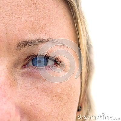 Het gezicht van de vrouw met kleurrijke blauwe ogen.
