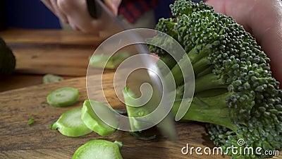 Het gezonde voedsel, kok snijdt een bos van broccoli Gezond assortiment van groenten en vruchten met peulvruchten stock videobeelden