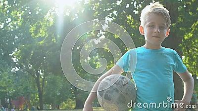 Het glimlachen van mannelijke jongen die buiten voetbal houdt op zomerzonnige dag, gezonde activiteit stock videobeelden