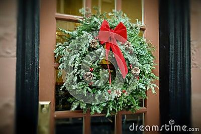 Het hangen van de Kroon van Kerstmis van Antiqued op deur