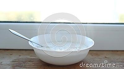 Het havermeel wordt beslagen op de vensterbank is stoom, ontbijt, close-up, ochtend stock videobeelden