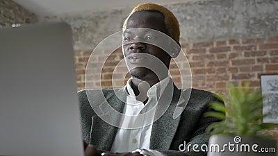 Het jonge Afrikaanse blondezakenman typen op laptop en het zitten in modern bureau, zeker, het lachen stock video
