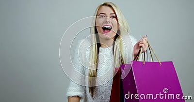 Het jonge blonde vrouwelijke model maakt uitdrukkingen van opwinding met het winkelen kleurrijke pakketten in haar handen stock video