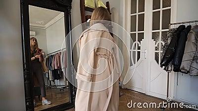 Het jonge blondy meisje neemt thebeige laag van het rek met verscheidenheid van uitrustingen en probeert het op haar schouders Bi stock video