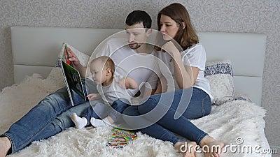 Het jonge familie spelen op bed thuis Mamma en Papaspel met hun dochter stock videobeelden